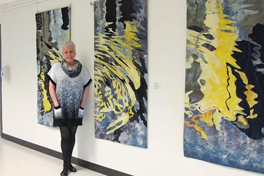 Fiber Artist Barbara Schneider and her artwork.  Photo credit, Barbara Schneider Textile Artist Facebook Page